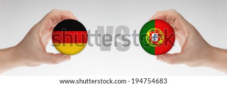 Man's hands holding styrofoam balls with German and Portuguese flag against the white background. - stock photo