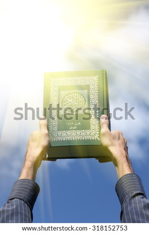 Man's hands holds Koran - holy book of muslims, on blue sky with clouds. With instagram style filter - stock photo