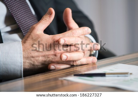 Man's hands in a thinking gesture during a meeting or negotiation - stock photo