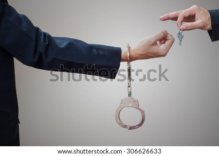 Man's hands in handcuffs and key - stock photo