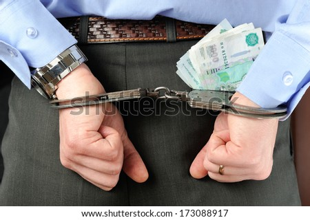 Man's hands in handcuffs and money in trouser pocket - stock photo