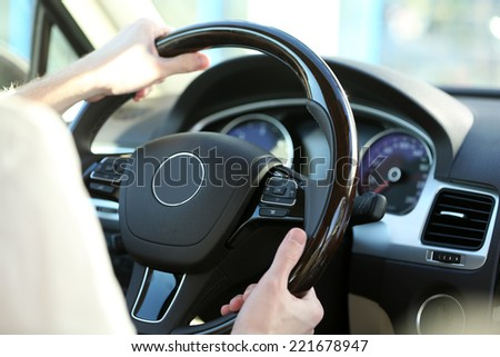 Man's hands on a steering wheel - stock photo