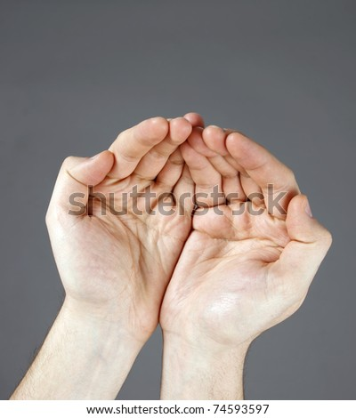 Man?s hands open isolated on grey background - stock photo