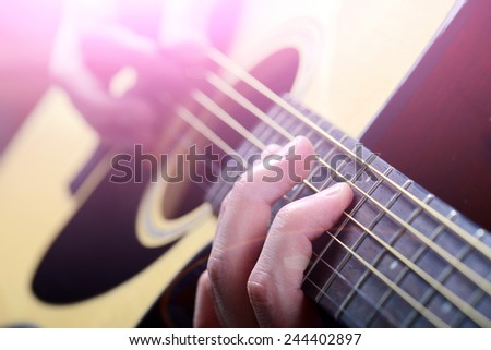 man's hands playing acoustic guitar, close up - stock photo