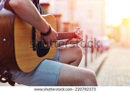 Man's hands playing guitar. Close up portrait  - stock photo