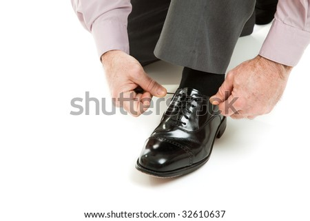 Man's hands tying shoelace of his new oxford shoes.  Isolated on white. - stock photo