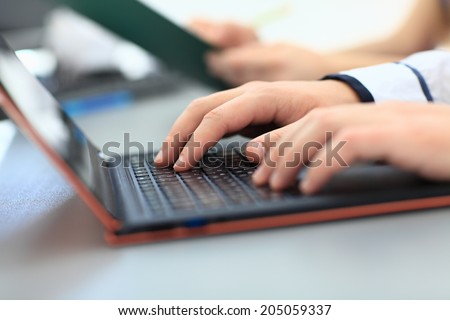 Man's hands typing on laptop keyboard - stock photo