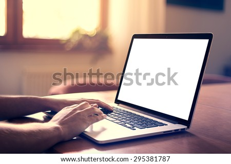 Man's hands using laptop with blank screen on desk in home interior. - stock photo