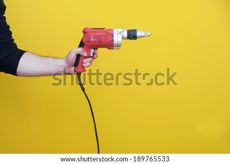 Man's left hand handling an electric drilling machine, isolated. - stock photo