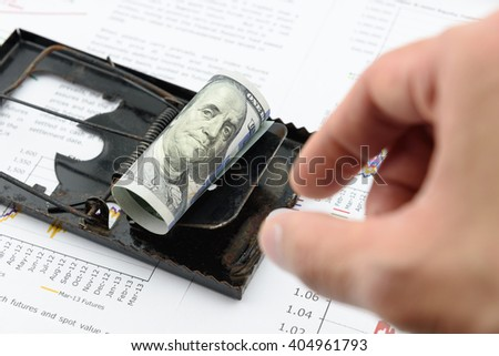 Man's right hand is preparing to pick a rolled up scroll of US 100 dollar bill with portrait / image of Benjamin Franklin on a black rat trap. Using money as a bait to lure someone for illegal things. - stock photo