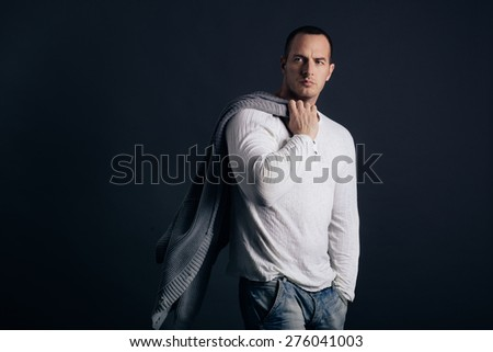Man's style. Male model posing in studio on dark background. Casual outfit - stock photo