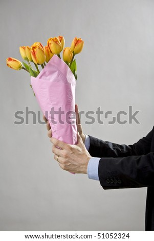 Man's two hands holding a bouquet of orange tulips - stock photo
