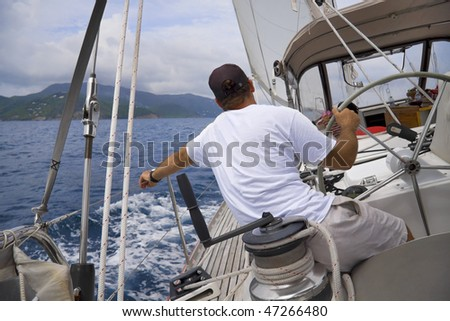 Man sailing a sailboat in the tropics with tropical mountain in background. - stock photo
