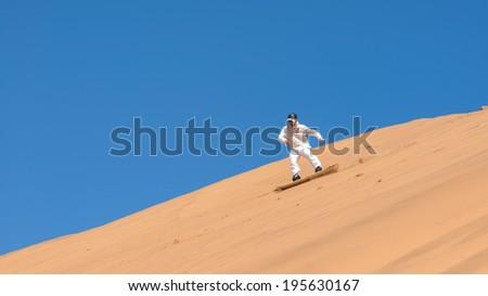 Man sandboarding in Namibia, Africa - stock photo