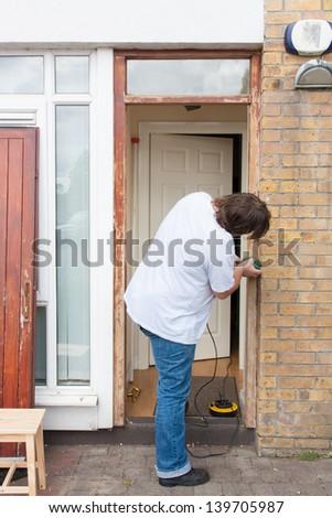 Man sanding down the front door - stock photo