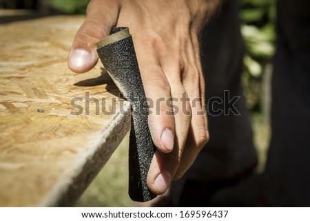 Man sanding wooden panel. - stock photo