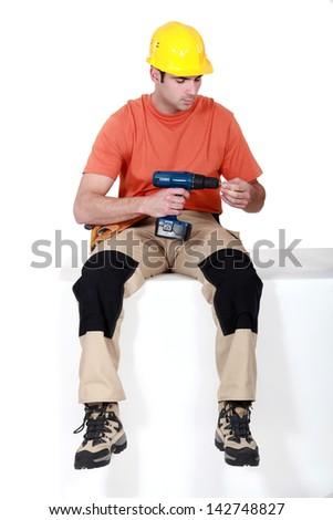 Man sat holding cordless drill - stock photo