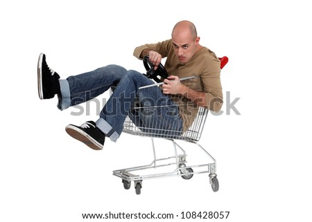 Man sat in shopping trolley with steering wheel - stock photo