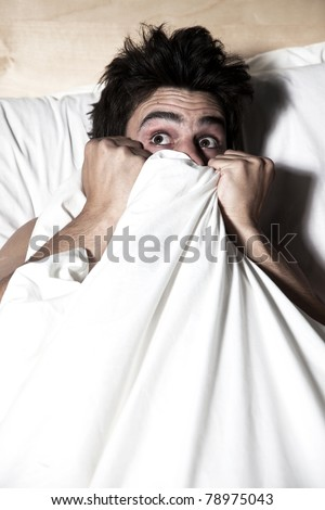 Man scared in the bed - stock photo