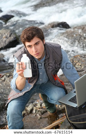 Man scientist testing quality of water in river - stock photo