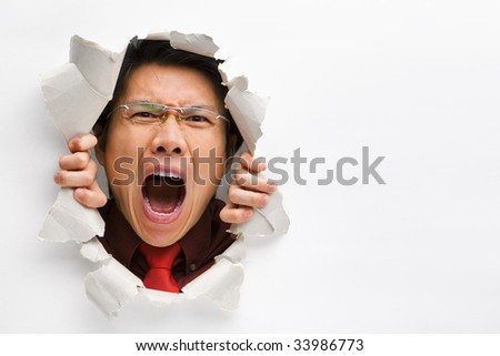Man screaming from the hole in wall with copy space in horizontal position - stock photo