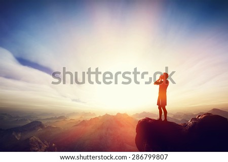 Man screaming on the top of the mounain at sunset. Concept of message, calling for help etc.  - stock photo