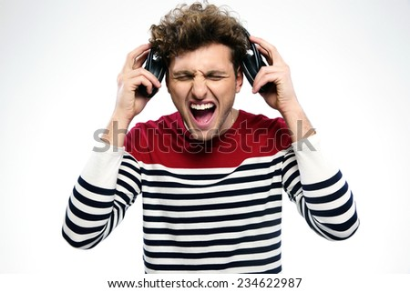 Man screaming while listening to music over gray background - stock photo