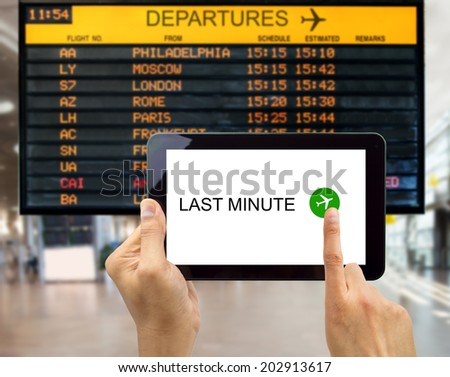 man search for last minute deals at an airport with your tablet - stock photo