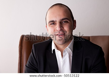 Man seated on a chair, smiling - stock photo