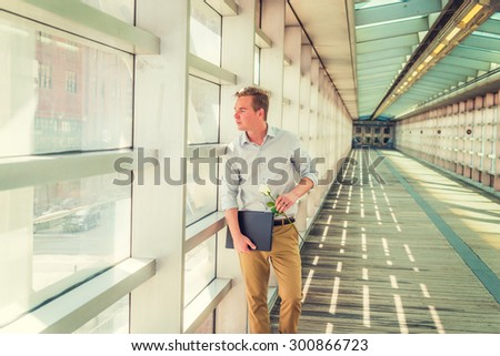 Man seeking love in New York. Wearing white shirt, yellow pants, carrying laptop computer, holding white rose. a young guy standing on walk way, looking outside, waiting for you. Instagram effect.  - stock photo
