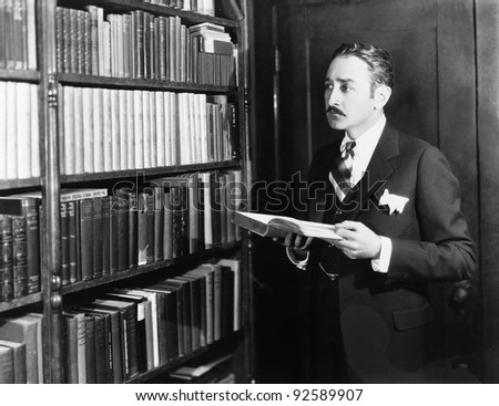Man selecting books from bookshelf in a library - stock photo