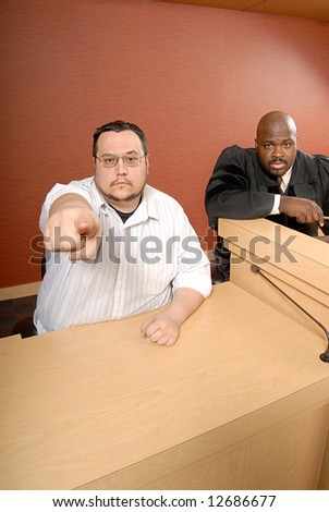 Man serving as a witness as trial pointing at the viewer - stock photo