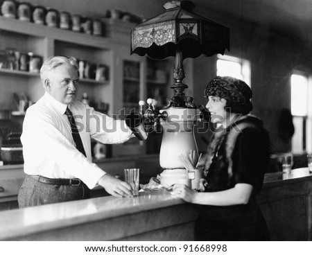 Man serving beverage to woman at counter - stock photo