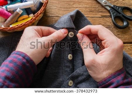 man sews a button to his shirt - stock photo