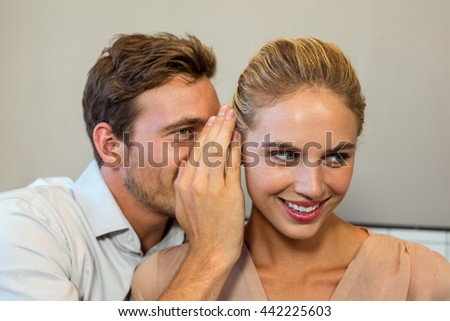 Man sharing secret with female colleague in office - stock photo
