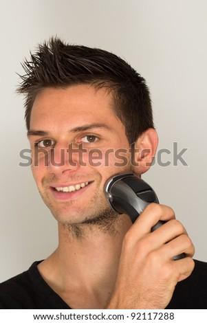 Man shaving face with electric razor - stock photo