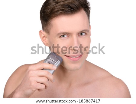 Man shaving. Handsome young shirtless man shaving with electric razor - stock photo