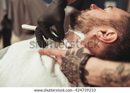 man shaving his beard in the professional hairdresser - stock photo