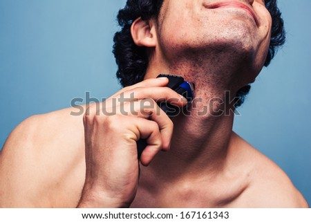 Man shaving with electric razor - stock photo