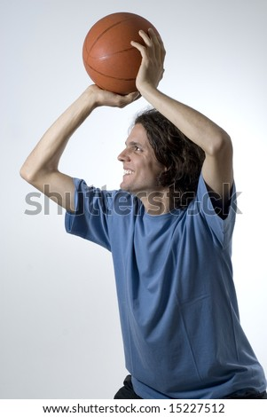 Man shooting a basketball with a smile on his face. Vertically framed photograph. - stock photo