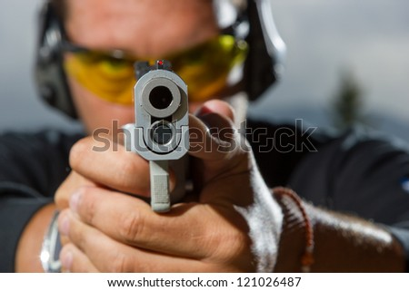 Man shooting on an outdoor shooting range, selective focus - stock photo