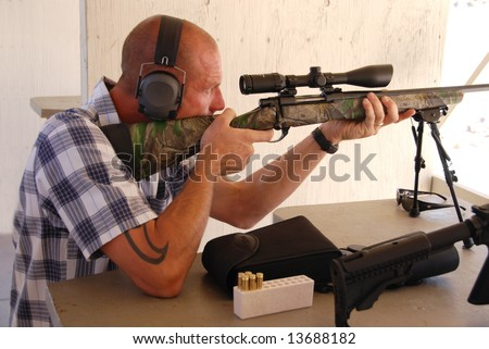 Man shooting sniper rifle. - stock photo