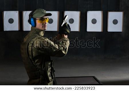 Man shooting with gun at a target in shooting range - stock photo