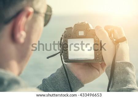 Man shoots at camera sea landscape at sunset. - stock photo