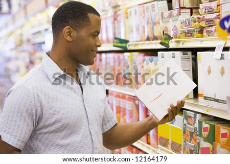 Man shopping in supermarket checking contents of packet - stock photo