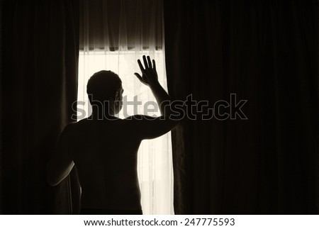 Man shot against the light of a window  - stock photo