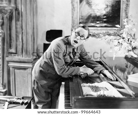Man shouting with his hand caught in a piano - stock photo