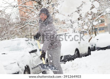 Man shoveling her parking lot after a winter snowstorm. - stock photo