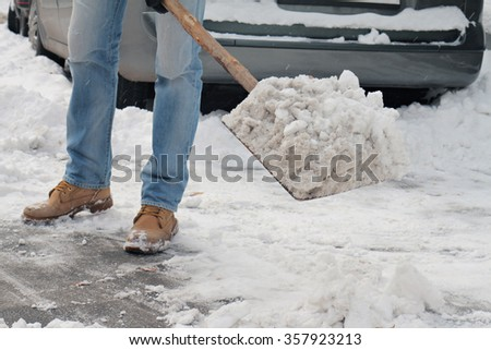 Man shoveling snow close up. Man cleaning snow from  sidewalk in front of  house. - stock photo