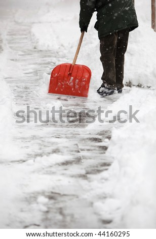 Man shoveling snow from the sidewalk in front of his house after a calamitous snowfall in a city - stock photo